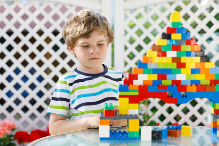 Little blond child playing with lots of colorful plastic blocks. Adorable preschool kid boy wearing colorful shirt and having fun with building big castle and creating a house