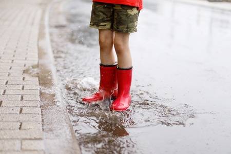 Child wearing red rain boots jumping into a puddle. Close up. Kid having fun with splashing with water. Warm heavy summer rain and happy children.
