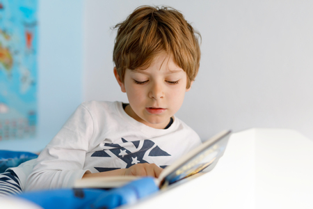 Cute blond little kid boy in pajamas reading book in his bedroom. Excited child reading loud, sitting in his bed. Schoolkid, family, education. Standard-Bild
