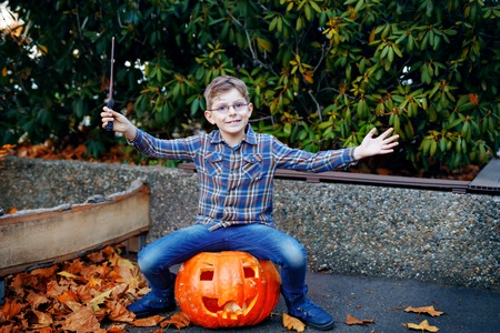 Beautiful kid boy in costume as a magician. Happy healthy child celebrating Halloween. Boy with glasses outdoors on autumn day.