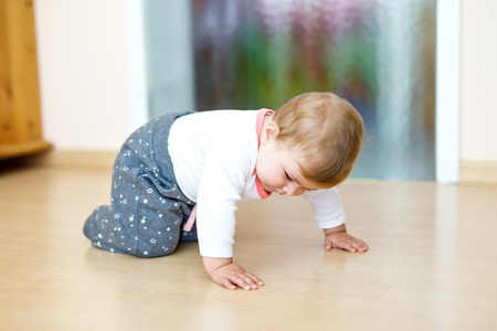 Little cute baby girl learning to crawl. Healthy child crawling in kids room. Smiling happy healthy toddler girl. Cute toddler discovering home and learning different skills