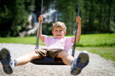 Funny kid boy having fun with chain swing on outdoor playground while being wet splashed with water. child swinging on summer day. Active leisure with kids. Happy crying boy with rain drops on face. Imagens - 112741977