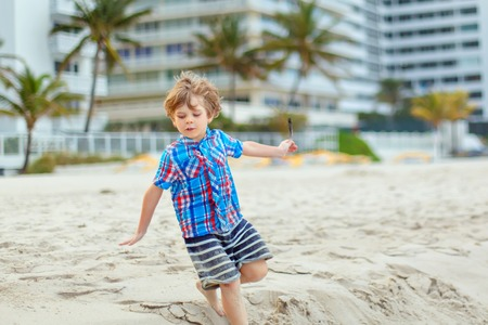 Portrait of happy little kid boy on the beach of ocean. Funny cute child making vacations and enjoying summer. Healthy boy on the beach of Miami USA on stormy windy day. Reklamní fotografie