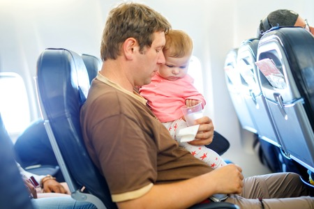 Young tired father and his crying baby daughter during flight on airplane going on vacations. Dad holding baby girl on arm. Air travel with baby, child and family concept