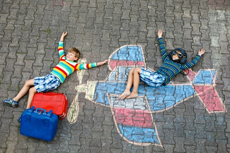 Two little children, kids boys having fun with with airplane picture drawing with colorful chalks on asphalt. Friends painting with chalk and going on vacations dreaming of pilot profession. Archivio Fotografico