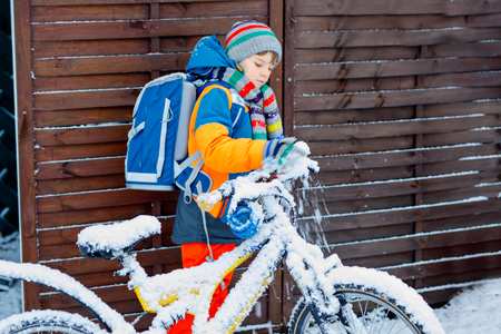 Little school kid boy of elementary class walking to school during snowfall. child removing snow from bicycle. Student with backpack or satchel in colorful winter clothes.