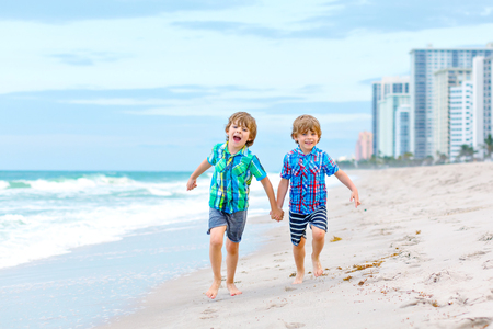 Two happy little kids boys running on the beach of ocean. Funny cute children, sibling and best friends making vacations and enjoying summer on stormy windy day. Healthy kids on beach of Miami, USA