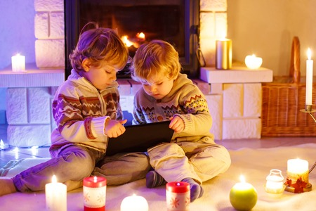 Two little children sitting by a fireplace at home on Christmas time. Happy cute adorable toddler boys, blond twins playing with new tablet gift. Family celebrating xmas holiday. Reklamní fotografie