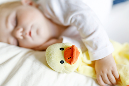 Cute adorable baby girl of 6 months sleeping peaceful in bed at home. Closeup of beautiful calm child, little newborn kid sleeping with plush toy duck.