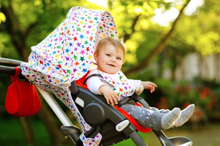 Cute healthy little beautiful baby girl sitting in the pram or stroller and waiting for mom. Happy smiling child with blue eyes. With green tree background. Baby daughter going for a walk with family Reklamní fotografie