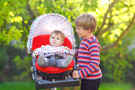 Little blond kid boy playing with baby sister. Happy siblings in garden. Baby girl sitting in pram or stroller. Brother and cute toddler outdoors, on summer day going for a walk together Reklamní fotografie
