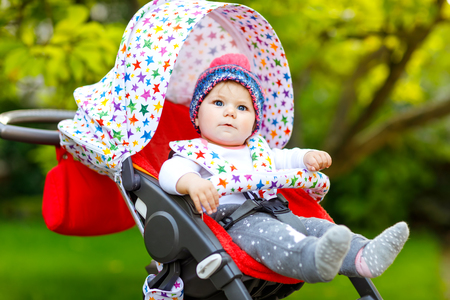 Cute healthy little beautiful baby girl with blue warm hat sitting in the pram or stroller and waiting for mom. Happy smiling child with blue eyes. baby daughter going for a walk with family