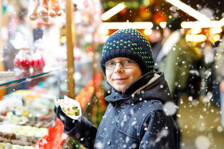 Little kid boy, cute child eating bananas covered with chocolate, marshmellows and colorful sprinkles near sweet stand with gingerbread and nuts. Happy boy on Christmas market in Germany. Reklamní fotografie