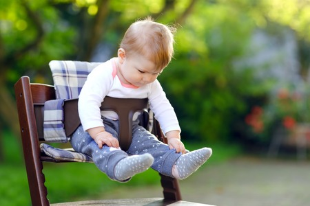Cute adorable baby girl sitting in high chair outdoors. Beatuiful child of 6 months in home garden, playing on warm sunny day. Healthy baby smiling and laughing. Reklamní fotografie