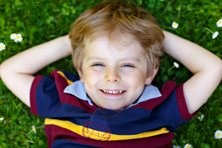 Happy little blond child, kid boy with blue eyes laying on the grass with daisies flowers in the park. Reklamní fotografie