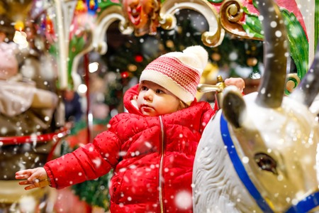 Adorable little kid girl riding on a merry go round carousel horse at Christmas funfair or market, outdoors. Happy toddler child having fun on traditional family xmas market in Germany Reklamní fotografie