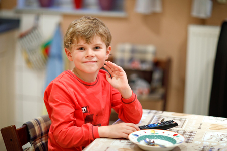cute little kid boy watching tv in the evening before going to bed. Healthy happy child having fun with cartoons on television. Kid at home in the kitchen.