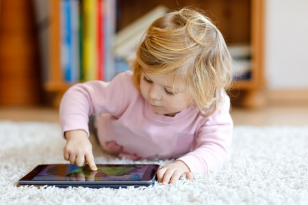 Cute little toddler girl playing with tablet pc at home. Healthy baby touching pad with fingers, looking cartoons and having fun with educational games on computer. Early development concept