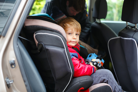 Portrait of pretty toddler boy sitting in car seat. Child transportation safety. Father clips on another son on background. Cute healthy kid boy with toy happy about family vacations with car