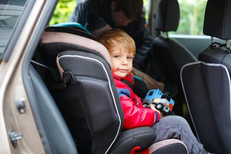 Retrato de niño bonito sentado en el asiento del coche. Seguridad en el transporte de niños. El padre graba a otro hijo en el fondo. Chico lindo niño sano con juguete feliz de vacaciones familiares con coche Foto de archivo