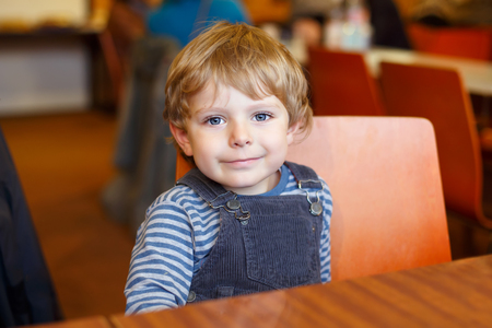 Portrait of cute beautiful toddler kid boy waiting in canteen of kindergarten for meal. Healthy happy child looking at the camera, indoors at nursery or home.