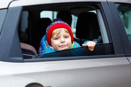 Portrait of pretty toddler boy sitting in car seat. Child transportation safety. Cute healthy kid boy looking happy about family vacations with car through window during standing in traffic jam Reklamní fotografie