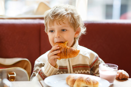 Cute healthy kid boy eating croissant and drinking strawberry milkshake in cafe. Happy child having breakfast with parents or at nursery. Vegetables, eggs as healthy food for children. Reklamní fotografie