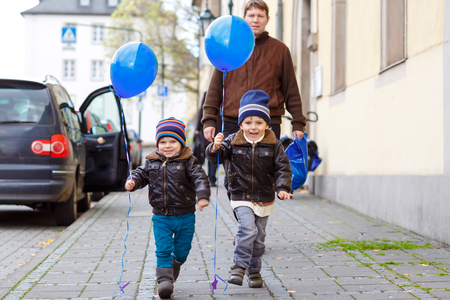 Two little kids boys and dad playing with blue air balloons outdoors. Happy twins and toddler brothers and father, young man together. Healthy children walking on street on cold day in warm clothes.