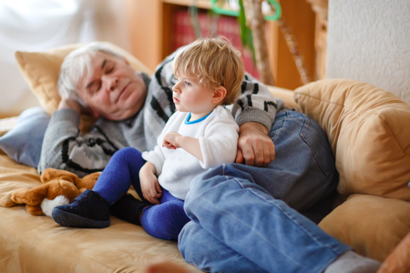 cute little toddler boy and grandfather watching together tv show. Baby grandson and happy retired senior man sitting together at home with cartoons on television. Calm family time. Reklamní fotografie