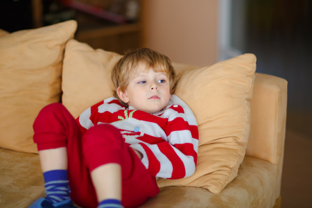 Happy adorable kid boy watching television while lying. Funny healthy child enjoying cartoons. Addiction concept. Toddler looking shows and film on tv at home.