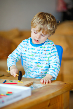 Cute toddler boy playing with wooden hammer tool at home in workshop. Kid boy play as handyman. Child in night clothes playing as builder or repairer, repairing or handcrafting. Handcrafting concept.
