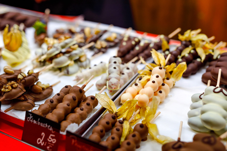Bananas, strawberries, raspberries and apples covered with chocolate and various glazes for sale in a shop window. Selling sweets at the Christmas market. In German price for raspberries. Reklamní fotografie