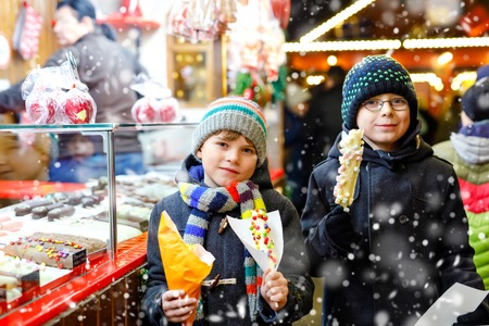 Two little kid boys, cute siblings eating bananas covered with chocolate, marshmellows and colorful sprinkles near sweet stand with gingerbread and nuts. Happy children on Christmas market in Germany. Reklamní fotografie