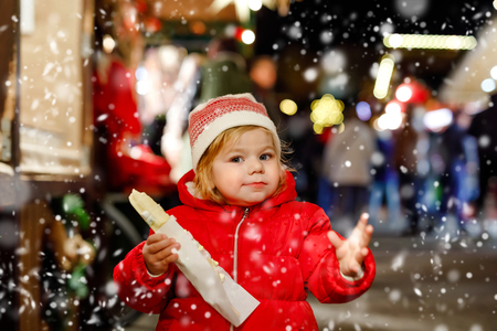 Little baby girl, cute child eating bananas covered with chocolate, marshmellows and colorful sprinkles near sweet stand with gingerbread and nuts. Happy toddler on Christmas market in Germany.