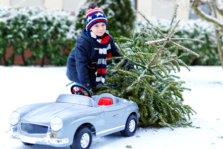 Healthy little smiling kid boy driving toy car with Christmas tree. Happy child in winter fashion clothes bringing hewed xmas tree from snowy forest. Family, tradition, holiday.