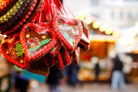 Gingerbread Hearts at German Christmas Market. Nuremberg, Munich, Berlin, Hamburg xmas market in Germany. On traditional ginger bread cookies written Merry Chrismtas called Lebkuchen in German