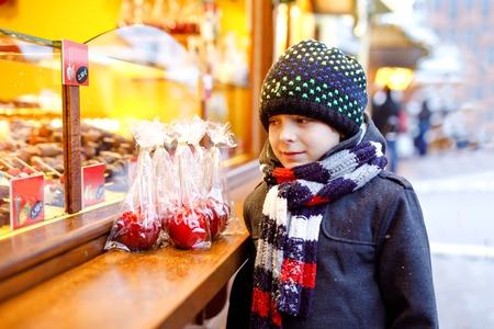 Little cute kid boy near sweet stand with sugared apples and chocolate fruits. Happy child on Christmas market in Germany. Traditional leisure for families on xmas. Holiday, celebration, tradition.