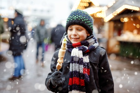 Little cute kid boy eating white chocolate covered fruits on skewer on traditional German Christmas market. Happy child on traditional family market in Germany during snowy day.