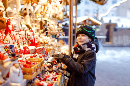 Little cute kid boy selecting decoration on Christmas market. Beautiful child shopping for toys and decorative ornaments stuff for tree. Xmas market in Germany.