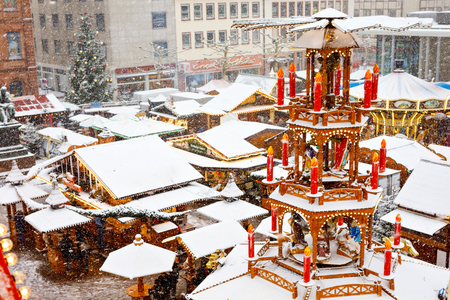 Traditional German christmas market in the historic center of a city in Germany during snow. Stands, traditional pyramid with candles on winter day 스톡 콘텐츠