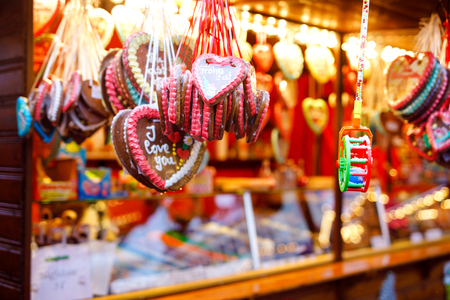 Gingerbread Hearts at German Christmas Market. Nuremberg, Munich, Berlin, Hamburg xmas market in Germany. On traditional ginger bread cookies written Merry Chrismtas called Lebkuchen in German