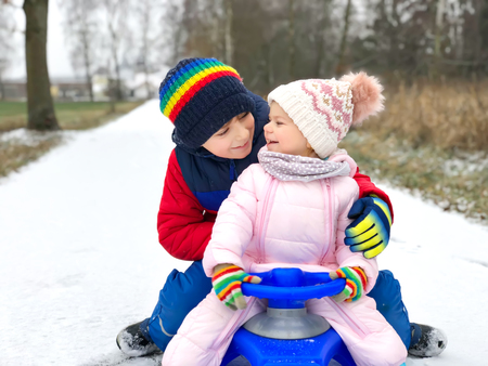 Little kid boy and cute toddler girl sitting together on sledge. Siblings, brother and baby sister enjoying sleigh ride during snowfall. Children sledding on snow. Active fun for family vacation Reklamní fotografie