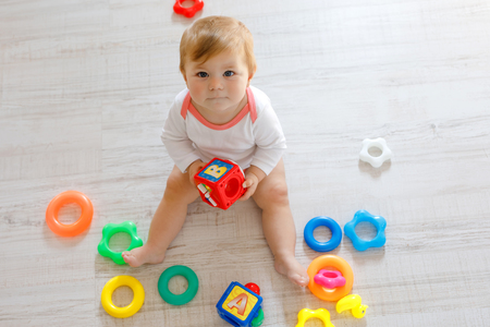 Adorable baby girl playing with educational toys in nursery. Happy healthy child having fun with colorful different toys at home. Kid trying to build plastic pyramid and using blocks with letters Reklamní fotografie