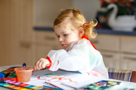 Cute adorable baby girl learning painting with water colors. Little toddler child drawing at home, using colorful brushes. Healthy happy daughter experimenting with colors, water at home or nursery Фото со стока