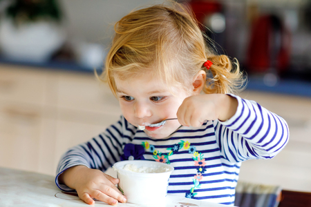 Adorable baby girl eating cottage cheese from spoon, healthy milk snack. Cute healthy toddler child, daughter with spoon sitting in highchair and learning to eat by itself in kitchen or nursery