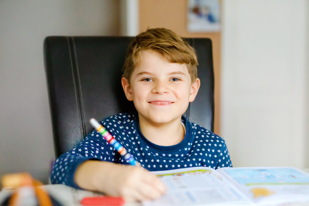 Happy smiling little kid boy in pajamas at home making homework at the morning before the school starts. Little child doing excercise, indoors. Elementary school and education: Boy writing letters Stok Fotoğraf