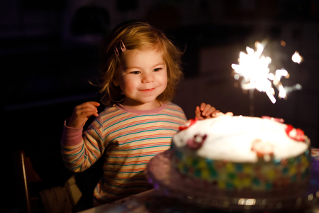 Adorable little toddler girl celebrating second birthday. Baby child eating marshmellows decoration on homemade cake, indoor. Happy healthy toddler is suprised about firework sparkler on cake