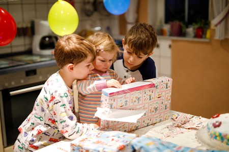 Adorable little toddler girl celebrating second birthday. Baby child and two kids boys unpacking gifts. Happy healthy children siblings is suprised about big boxes and toys