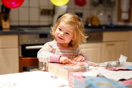 Adorable little toddler girl celebrating second birthday. Baby child unpacking gifts. Happy healthy child is suprised about big boxes and toys present Stock Photo