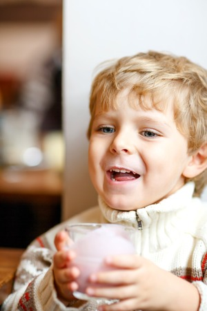 Happy little blond kid boy drinking milk or strawberry milkshake for breakfast or lunch. Healthy eating for children. Happy child in colorful clothes having breakfast